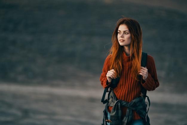 Femme dans un pull rouge et avec un sac à dos sur son dos modèle de jeans randonnée en montagne