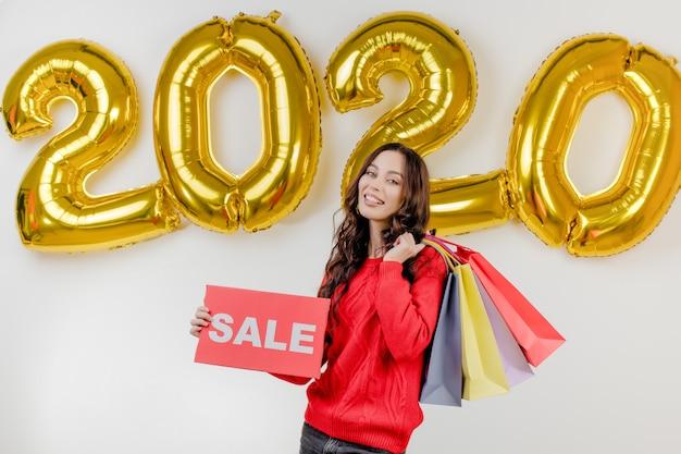 Femme, dans, pull rouge, tenue, coloré, sacs, et, copyspace, vente, signe, devant, 2020, nouvel an, ballons