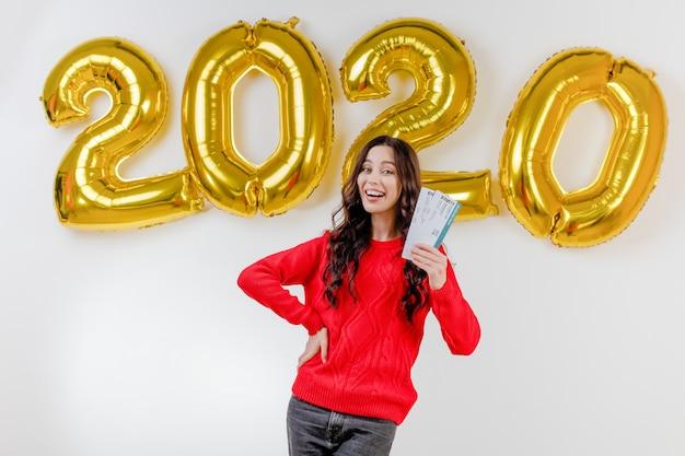 Femme, dans, pull rouge, tenue, modèle, billets avion, devant, 2020, nouvelle année, ballons