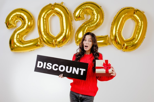 Femme, dans, pull rouge, tenue, noël, présent, et, fond, réduction, signe, devant, 2020, nouvel an, ballons