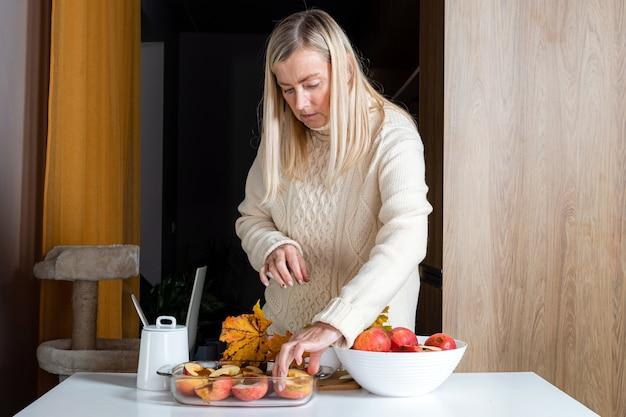 Femme dans un récipient en verre prépare les pommes pour la cuisson, le concept de cuisson du désert fait maison