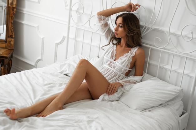 Femme dans une robe blanche dans la chambre sur le lit