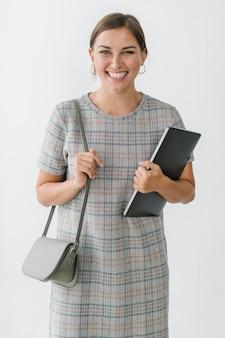 Femme dans une robe à carreaux grise tenant un ordinateur portable