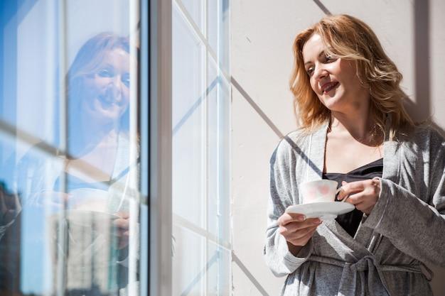 Une femme dans une robe de chambre d'argent se tient près de la fenêtre avec une tasse de boisson dans ses mains