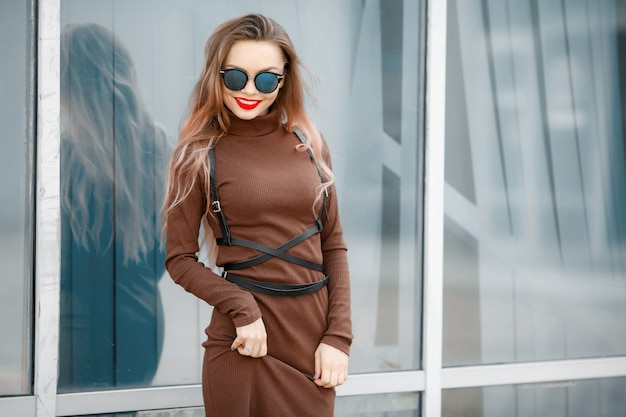 Une femme dans une robe dans la rue avec des lunettes et une ceinture en cuir