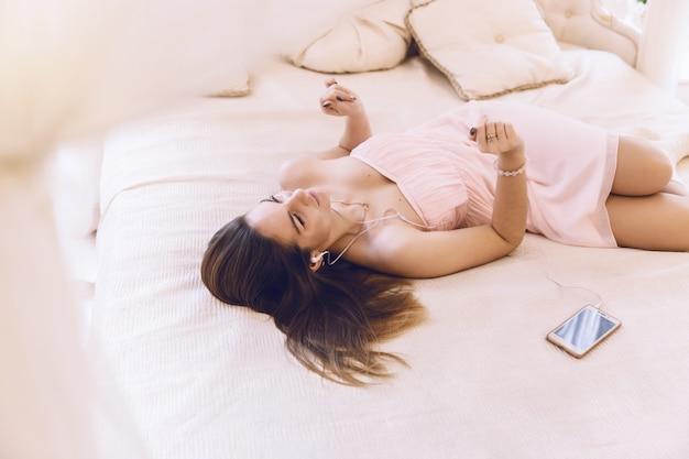 Femme dans une robe rose avec un casque d'écoute de la musique se trouvant à côté d'un téléphone portable