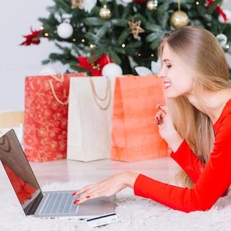 Femme, dans, robe rouge, coucher plancher, à, ordinateur portable