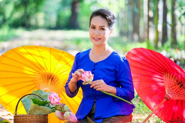 Une femme dans une robe thaïlandaise bleue tient une belle fleur de lotus.
