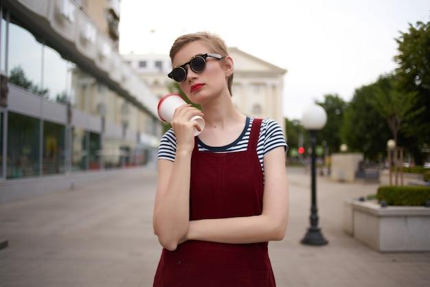 Femme dans la rue parlant au téléphone portant des lunettes en verre avec mode boisson