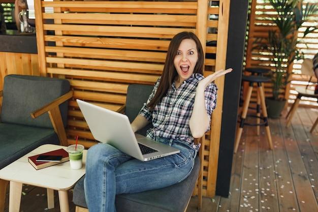 Femme dans la rue en plein air café d'été café en bois assis dans des vêtements décontractés, travaillant sur un ordinateur portable moderne