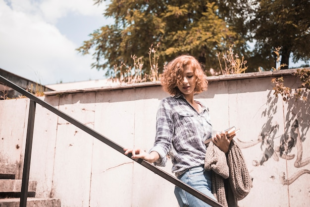 Femme, dans, rue, porter, à, livres, et, écharpe, dans, descendre, sur, escalier
