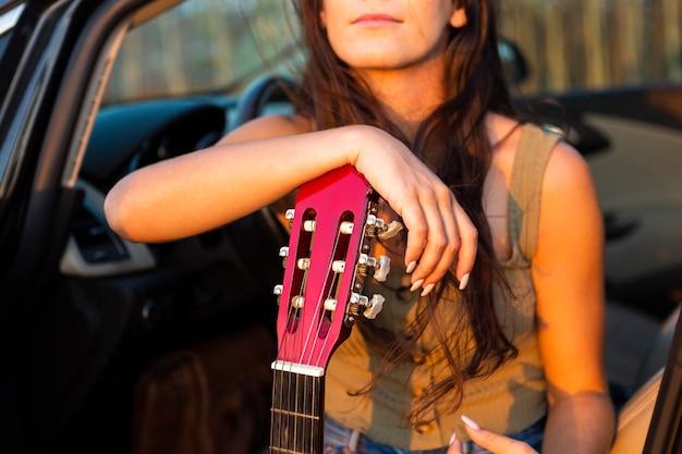 Femme dans sa voiture admirant le coucher du soleil tout en se reposant à la guitare