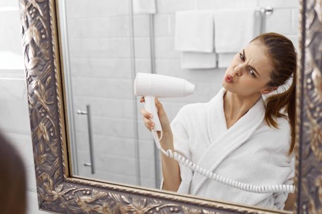 Femme dans la salle de bain cheveux secs et intérieur de la robe blanche