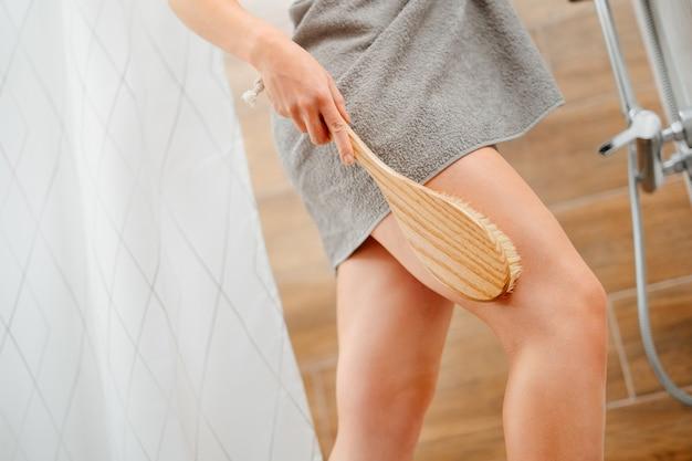 Une femme dans la salle de bain prend soin de la peau du corps avec une brosse de massage écologique