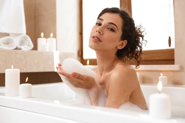 Femme dans la salle de bain se repose dans le bain.