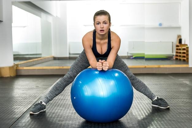 Femme dans une salle de sport, faire des exercices avec grosse boule