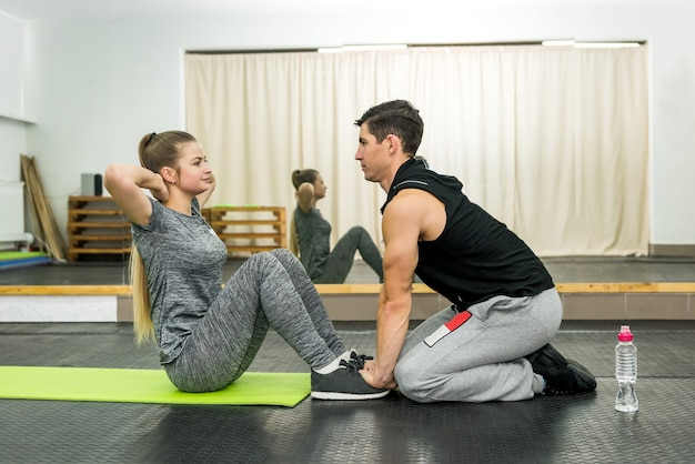 Femme dans une salle de sport, faire des exercices avec instructeur
