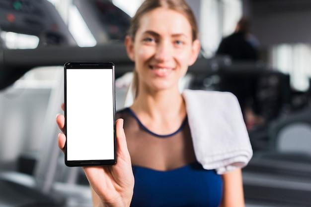 Femme dans une salle de sport avec un modèle de smartphone