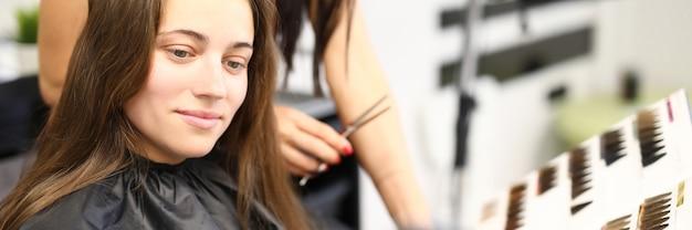 La femme dans le salon de beauté choisit la couleur de teinture de cheveux du catalogue