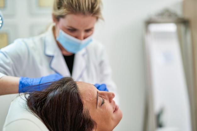 Femme dans un salon de beauté se faire des injections de botox sur la joue