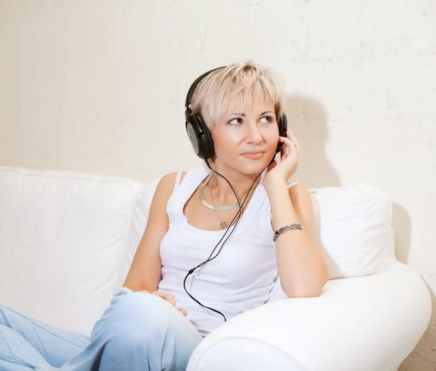 Femme dans le salon à l'écoute de lecteur mp3 en souriant