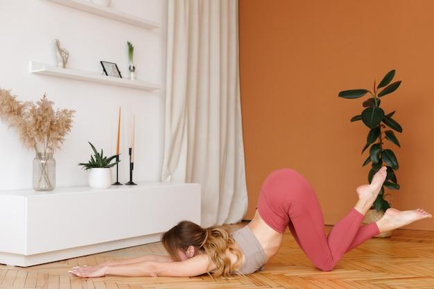 Femme dans le salon faisant du yoga à la maison