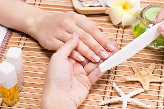 Femme dans un salon de manucure recevant une manucure par une esthéticienne. concept de traitement de beauté.