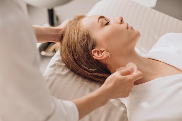 Femme dans un salon de soins de beauté avec pierre de gua sha