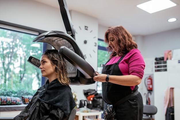 Femme dans un sèche-cheveux infrarouge professionnel de coiffeur