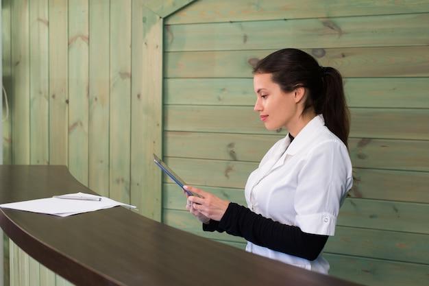 Femme dans un spa recpetion utilise texto tablet pc au client. concept de beauté et de technologie.
