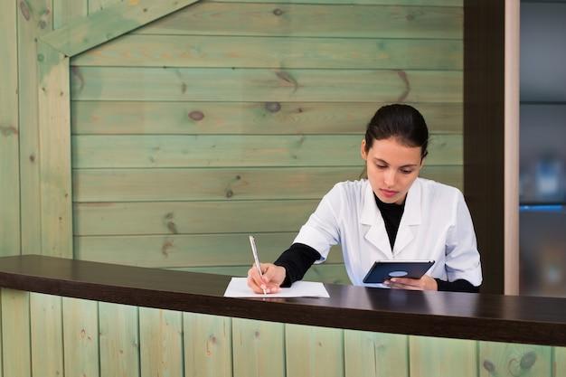 Femme dans un spa recpetion utilise textos tablet pc au client. concept de beauté et de technologie.