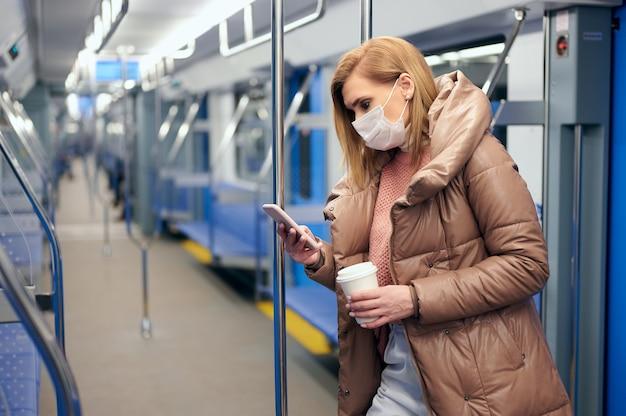 Une femme dans une station de métro portant un masque d'hygiène chirurgicale protecteur sur le visage empêche le risque de coronavirus