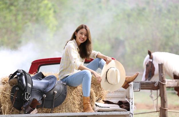 Une femme dans un style cowgirl est assise dans un ranch de chevaux avec un environnement agricole occidental.