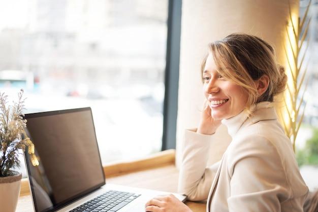 Femme dans une suite blanche travaillant sur un ordinateur portable au déjeuner d'affaires