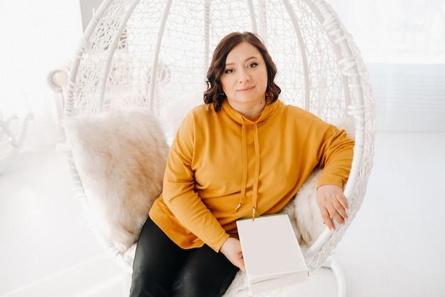 Une femme dans un sweat à capuche orange est assise sur une chaise inhabituelle avec un livre dans ses mains