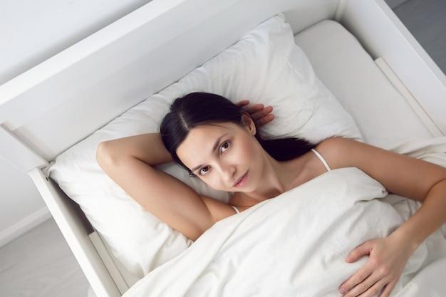 Femme dans un t-shirt blanc est allongée sur le lit et un oreiller est sous la couverture dans la chambre