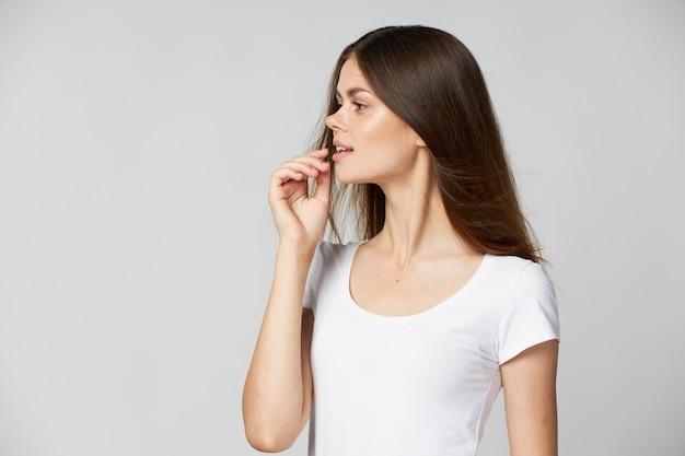 Femme dans un t-shirt blanc, il regarde sur le côté les cheveux longs main près du visage