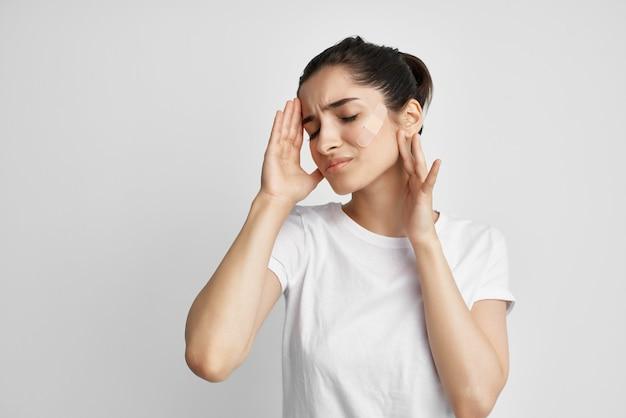 Femme dans un t-shirt blanc mal de tête négatif fond isolé. photo de haute qualité