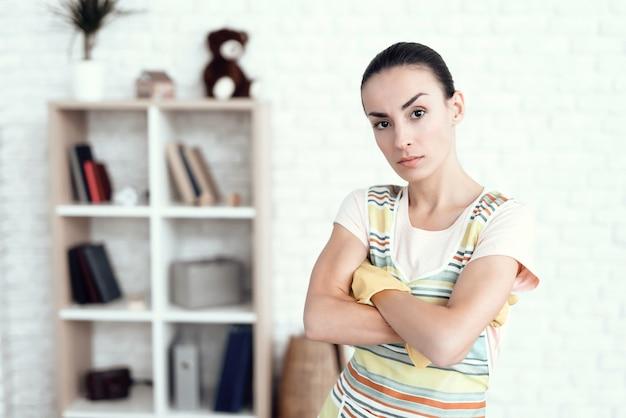 Une femme dans un t-shirt blanc posant à la maison avec des détergents
