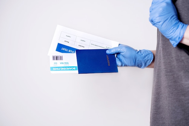 Une femme dans un t-shirt gris tenant des documents pour voyager en avion: passeport, billet, test pcr covid-19 sur un fond blanc, espace de copie. concept de voyage aérien covid-19.