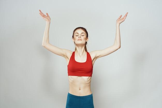 Une femme dans un t-shirt rouge sur un mur lumineux est engagée dans des gestes de remise en forme avec ses mains une silhouette mince