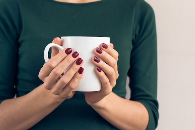 Femme, dans, a, t-shirt vert, et, a, manucure marron, tenue, tasse blanche