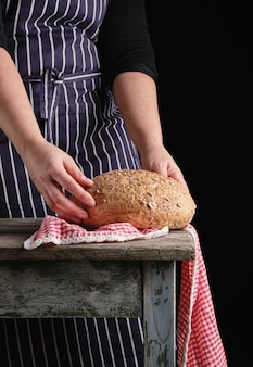 Femme dans un tablier rayé bleu tient dans ses mains cuit du pain de seigle rond