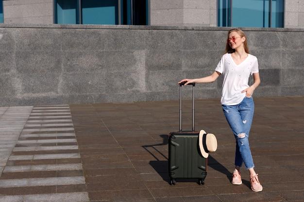 Femme dans un tshirt blanc et un jean bleu avec une valise l'été en voyage