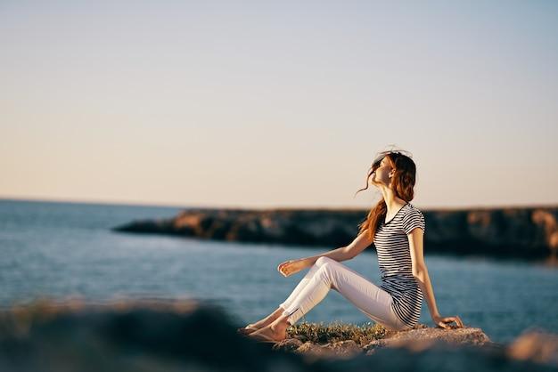Une femme dans un tshirt rayé et un pantalon blanc est assis sur la plage près de la mer dans les montagnes