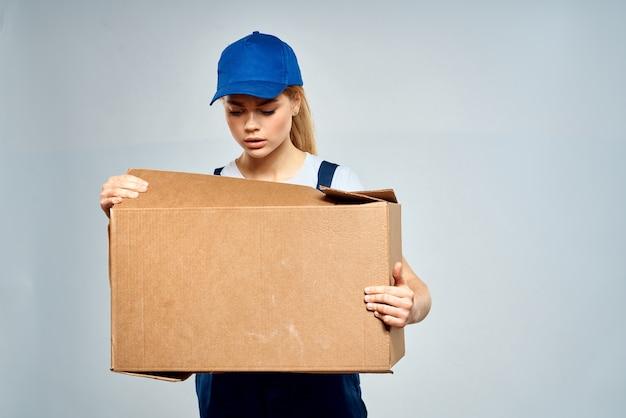 Une femme dans un uniforme de travail avec une boîte dans les mains d'un mur lumineux de service de livraison de services de livraison.
