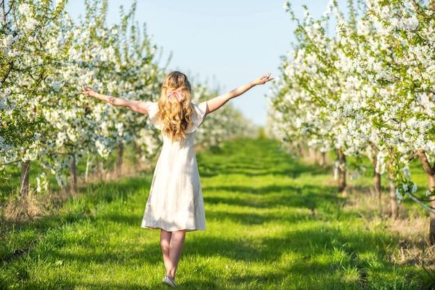 Femme dans un verger en fleurs de cerisier au printemps