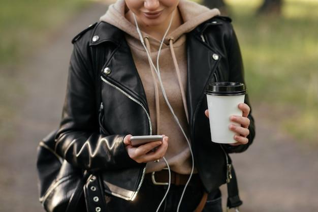 Une femme dans une veste en cuir avec un casque dans ses oreilles tient le téléphone dans sa main