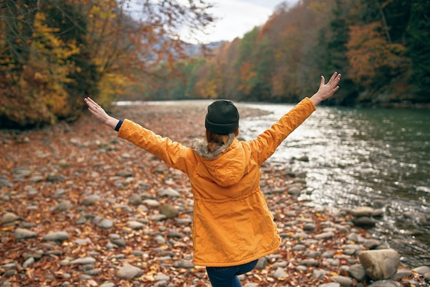 Femme dans une veste jaune voyage dans la rivière de la forêt d'automne