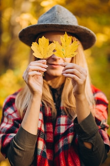Une femme dans une veste rouge et un chapeau gris couvre son visage avec des feuilles jaunes dans la forêt d'automne